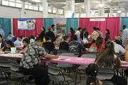 Job seekers fill out applications at the WorkForce 2013 job fair at the Neal S. Blaisdell Center.
