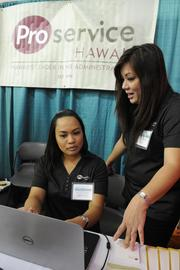 Agnes Okuma and Tami Minami  of ProService Hawaii schedule follow-up interviews for applicants at the WorkForce 2013 job fair.