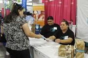 Brandy Burke, left a purchasing assistant at Turtle Bay Resort, and Human Resources Manager Grace Kamae accept a resume from a job applicant at their booth at the WorkForce 2013.