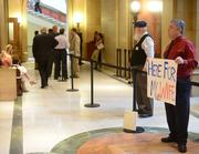 David Tollefson holds a sign outside of the House of Representatives