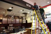 Workers install a sign at the Starbucks cafe that will operate inside Portland's Galleria CityTarget.