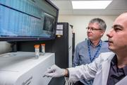 Dr. Stephen Kingsmore (left) and Darrell Dinwiddie work on the sequencing machine at Children's Mercy.