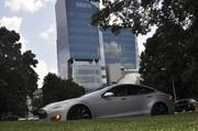 Tillis sits in the Tesla with the State Employees Credit Union building as backdrop.