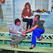 """Left to right (clockwise): The Playhouse's  Laura Michelle Wolfe, operations manager, Christina Casella, education and outreach director, and Asia Ciaravino, CEO, go over business reports on the set of """"Picnic,"""" a play currently showing in The Playhouse's Cellar Theater. The Playhouse team finagled all kinds of resources to create a realistic farmhouse settting, complete with grass."""