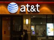 A pedestrian walks past an AT&T Inc. store in the Chinatown neighborhood of Washington, D.C. Photographer: Andrew Harrer/Bloomberg