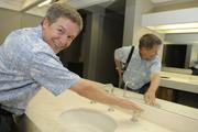 Ted Guth, CFO of Douglas Emmett Inc., tries out a faucet in the Honolulu Club's men's locker room, where new countertops, mirrors and fixtures have been installed.