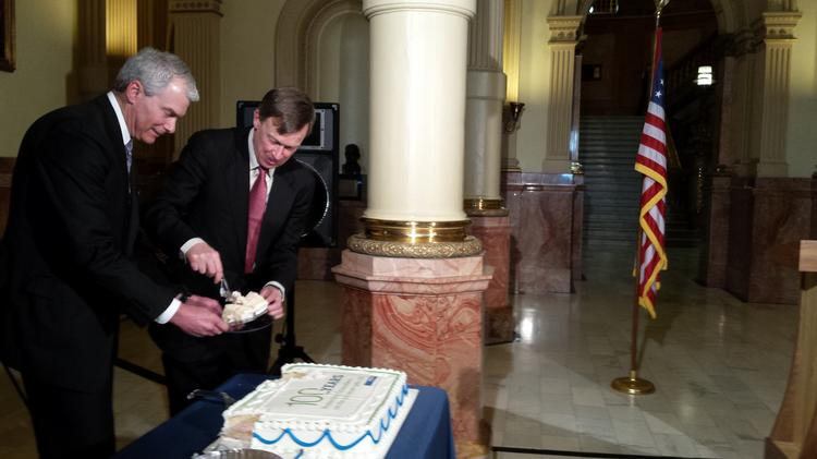 Pinnacol CEO Phil Kalin and Gov. John Hickenlooper sample cake at a 2015 ceremony marking the 100th anniversary of workers-comp insurance in the state. Now, Pinnacol is serving up a new kind of Cake.