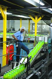 Kimberly Moore works with Mountain Dew bottles at Buffalo Rock, which reported steady revenue.