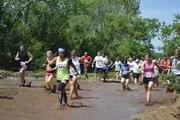 Gladiator Dash participants start off the race by running through mud.