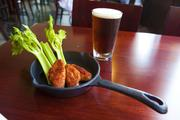 On the menu is OTR Butt Rub Wings. It is served with celery stalks in a cast iron skillet. The beer is Negra Modelo.