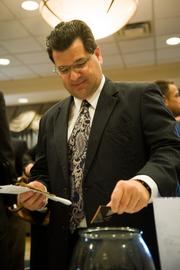 Paul Messineo of Allen & Shariff Engineering, LLC drops his business card into a fish bowl.