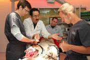 Dr. Luis Llerena, middle, assistant professor of surgery at USF and medical director of the Surgery & Interventional Training Center, instructs Cole Giering, Patrick Rees and Bobby Rohrlack in CAMLS trauma operating room. They are dealing with a double amputee mannequin, featured on next page.