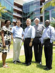 To the left, in front of the new UH Cancer Center are, from left, Pebbles Fagan, Dr. Herbert Yu, Joe Ramos, Dr. Brian Issell and James Turkson. Top, an exterior view of the UH Cancer Center.