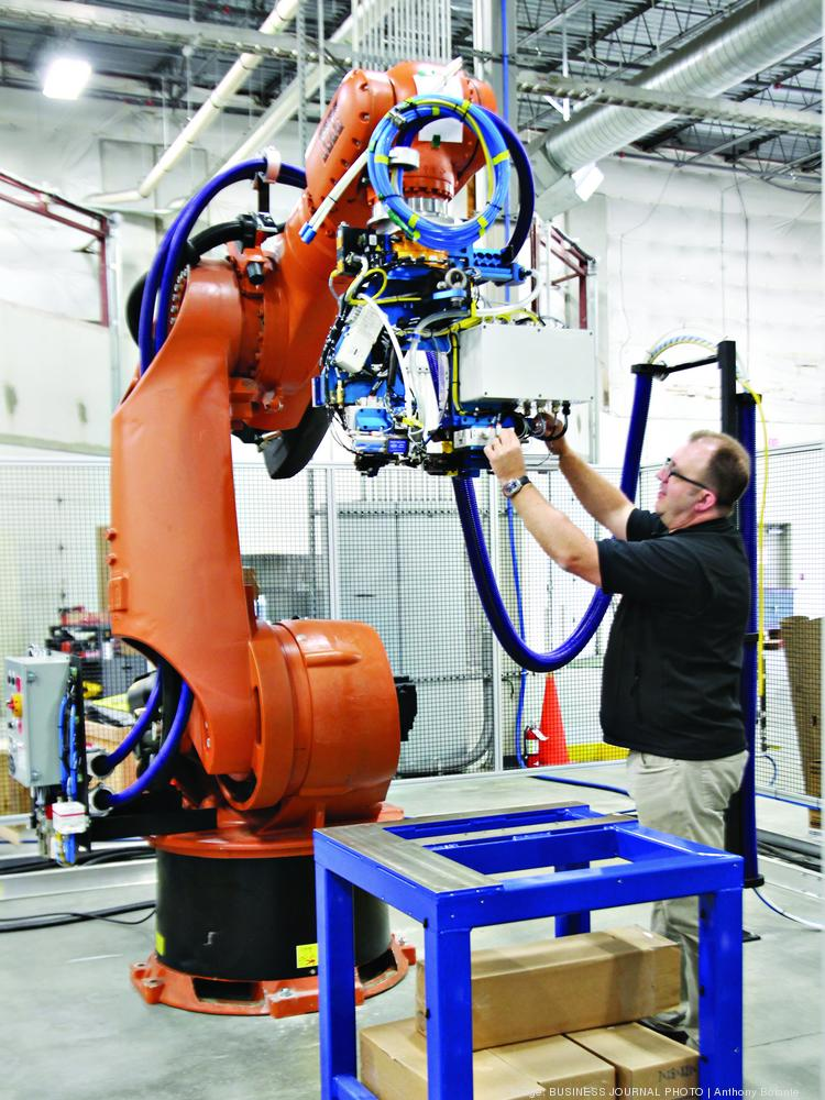 Mark Irby, KUKA Systems senior account manager, looks over a fastener robot. Robot arms like these are now operating inside the Boeing Everett plant, drilling and fastening some sections of 777 fuselages, as Boeing and KUKA engineers prove out the system.