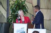 Charlotte Mayor Pro Tem Patrick Cannon presents Houston Mayor Annise Parker with a bottle of North Carolina wine as a thank you for her participation at the opening event held at the Petroleum Club of Houston.