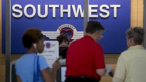 Travelers receive boarding passes at the Southwest Airlines Co. check-in counter at Ronald Reagan National Airport in Washington, D.C., U.S., on Friday, July 18, 2014. Southwest, the largest domestic airline in terms of passengers carried, is expected to