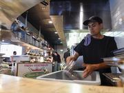 Dishwasher Eleazar Juarez puts away dishes at Ace Eat Serve.