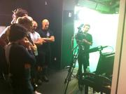 WWE athletes and support crew watch a play back of a green screen recording.