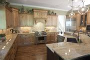 The kitchen in the Alexis by W.V. deStafano Homes LLC includes lots of woodwork and granite countertops.