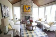 The Somerset Hills sun room features light colors and a fireplace as well as a wood ceiling.