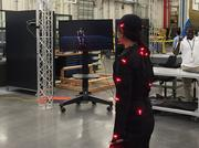 Boeing S.C. employee Sriya Ngo shows how a lighted suit will help the ergonomics team study motion and recommend workflow changes to prevent injuries to assembly and production workers.
