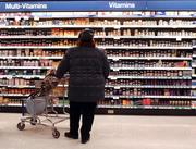 A shopper looks at the vitamin selection at a Walgreen's drug store.