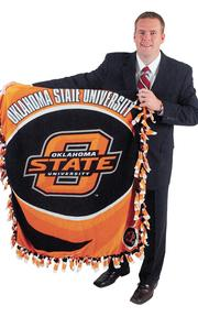 """Rick Griffin - Attorney, Martin, Pringle, Oliver, Wallace & Bauer LLP """"The prop used in the photo is an Oklahoma State University blanket, which is important to me for two reasons. First, I bleed orange and black (Go Pokes!). Second, the blanket actually belongs to my newborn daughter, made for her by a dear friend who passed away shortly after she made the blanket."""""""