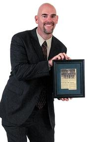 """Charles Koeber - Associate dean, Fairmount College of Liberal Arts and Sciences, and associate professor of sociology, Wichita State University """"In my picture I hold a newspaper photo of my freshman basketball team and my coach, Tom Leehy. We were a team of mediocre athletes at best, but we significantly improved and concluded by winning a tournament championship. I learned through that experience how much I could accomplish through hard work, discipline, teamwork and being able to think under pressure."""""""