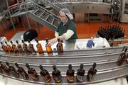 Mary Carney, a Jim Beam Brands Co. employee, checks the label quality on bottles of Jim Beam Black bourbon whiskey at their distillery in Clermont, Kentucky, U.S., on Tuesday, Feb. 8, 2011.