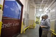 Jeremy Bowen, director of operations, and Sid Levy, senior director of communications and community relations, look at a new branding mural inside Snyder's-Lance Inc.'s Charlotte plant.