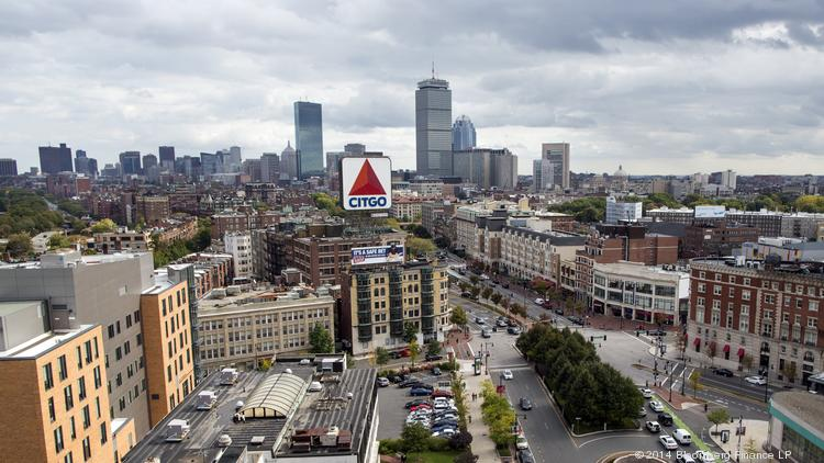 Kenmore Square, foreground, stands with the city skyline behind it.