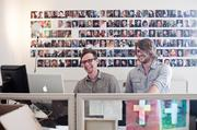 Producers Daniel Collins and Tommy Wilson review video content at StudioNow's offices on Hillsboro Pike. The wall of photos behind them features about 150 of the more than 6,000 filmmakers who work with the video production company.