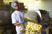 CORN BY THE KETTLE: Lonnie Jones pops yellow round popcorn at the company's plant in Kent. The popcorn is cooked at 530 degrees.