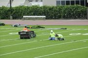 Workers tend to the details on the installation of new turf at Punahou School's Alexander Field.