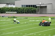 Workers install the yard lines on the new turf at Punahou School's Alexander Field.