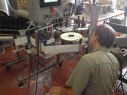 Employee Mike Washil monitors the labeling process as he and a colleague bottle beer.