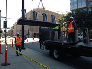 Workers install a bike kiosk in front of the San Jose convention center, part of a network of kiosks that will allow people to share bicycles throughout the Bay Area.