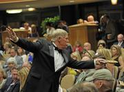 Bid spotter Tom Johnson gestures to Weber's camp, encouraging them to raise their bid.