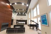 Metro Centre's two-story club room includes art work, a piano and couches.