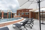 The rooftop pool deck at Metro Centre. The deck includes barbeques a fireplace and lounge seating.
