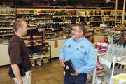 ABC Fine Wine & Spirits at 3015 W. Kennedy Blvd. is still open as construction of the new store on the same site progresses. Above, Neil Colledge, ABC's store manager, speaks with Bobby Hoos, GM of West Wind Provisions, after he restocked Boar's Head products in the store.