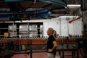 Distillery technician Laura Elden performs quality control along the Jim Beam Maple bourbon bottling line at the Beam Inc. distillery in Clermont, Kentucky, U.S., on Thursday, Aug. 1, 2013.
