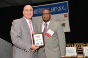A winner of the 2013 Minority Business Leader Awards presented by the Philadelphia Business Journal with editor Craig Ey.