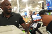 Sam's Club this week introduced a new feature for its mobile app that is expected to speed checkout at its Pineville store. Here, a customer uses the app by having his smartphone scanned to get his shopping total.