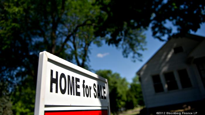 A for sale sign stands outside of a home in Princeton, Illinois, U.S., on Wednesday, May 30, 2012. The number of Americans signing contracts to buy previously-owned homes fell in April by the most in a year, indicating the U.S. housing recovery remains un