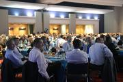 A table of Wells Fargo employees and guests listens to a panel discussion of the 2003 Super Bowl season.