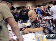 Comic book artist George Perez signs for fans at his table.