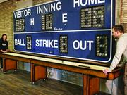 A scoreboard from the former County Stadium is used to keep score at shuffleboard at Direct Supply on Milwaukee's northwest side.