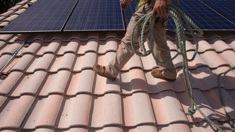 A solar installer prepares another row for panels.