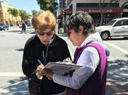"Jackie Strauss (left) signs a petition to place a rent control initiative on San Mateo's November ballot. ""She really talked me into it,"" Strauss said of signature collector Elizabeth Zarabanda (right). ""I don't really know anything about it, but I figured it couldn't hurt."""